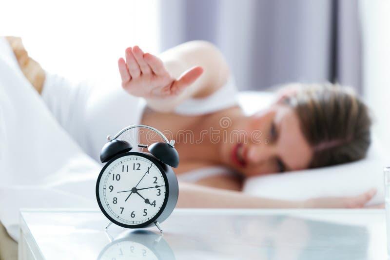 Boze jonge vrouw die de wekker van het bed thuis uitzetten stock foto