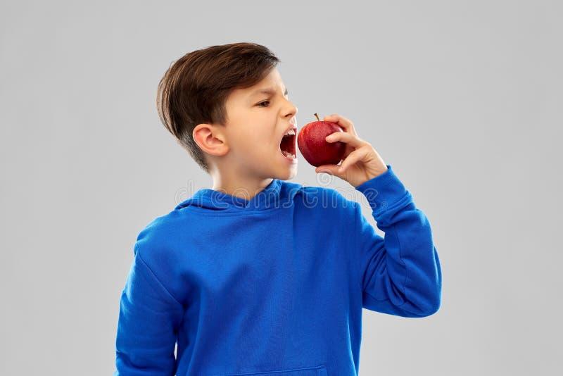 Boze jongen in blauwe hoodie met rode appel royalty-vrije stock foto's