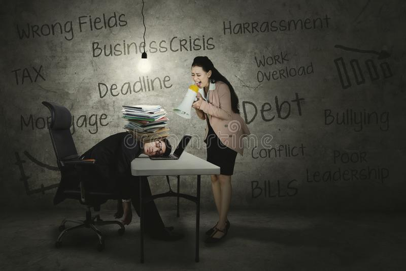 Boze leider die aan haar uitgeputte werknemer gillen stock afbeeldingen