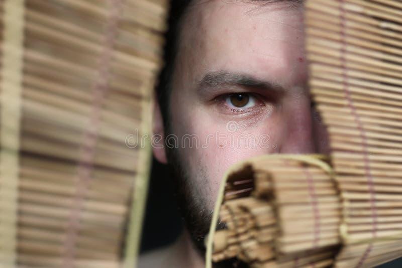 Boze mens bij de jaloezie stock fotografie