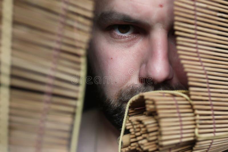 Boze mens bij de jaloezie royalty-vrije stock foto's
