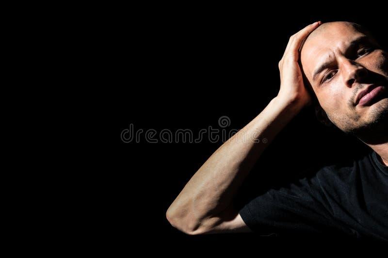 Boze Mens De boze en gefrustreerde mens leunde zijn hoofd op zijn hand stock afbeeldingen