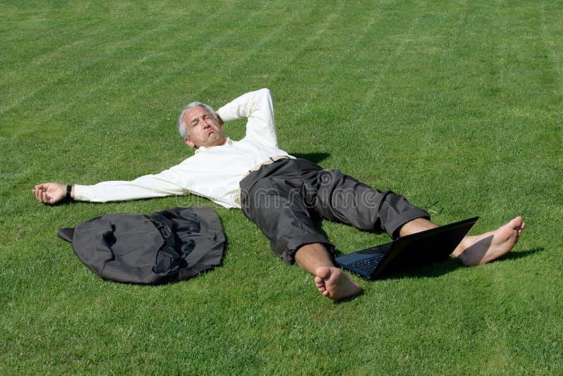 Boze mens die op gras ligt royalty-vrije stock foto