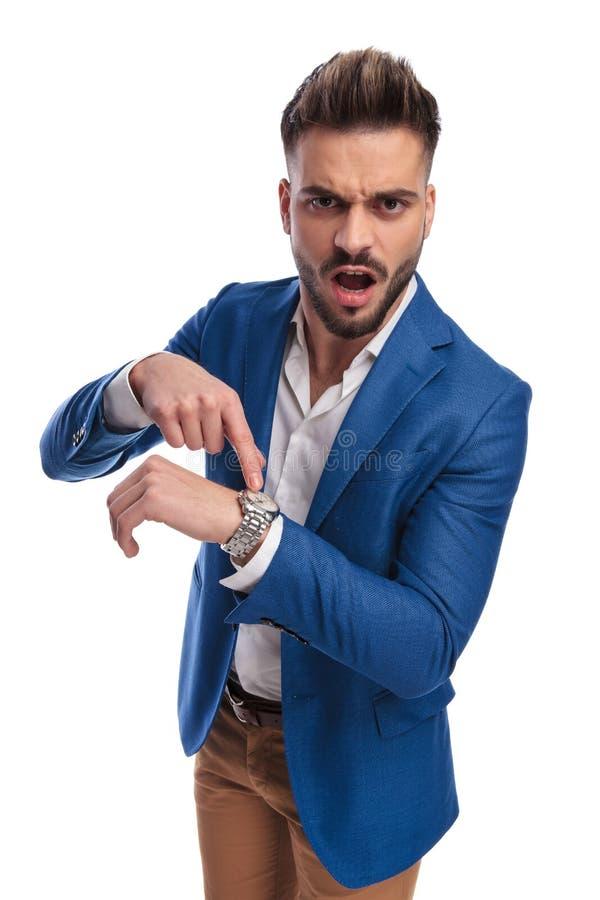 Boze mens die zijn vinger richten aan horloge en het gillen royalty-vrije stock fotografie