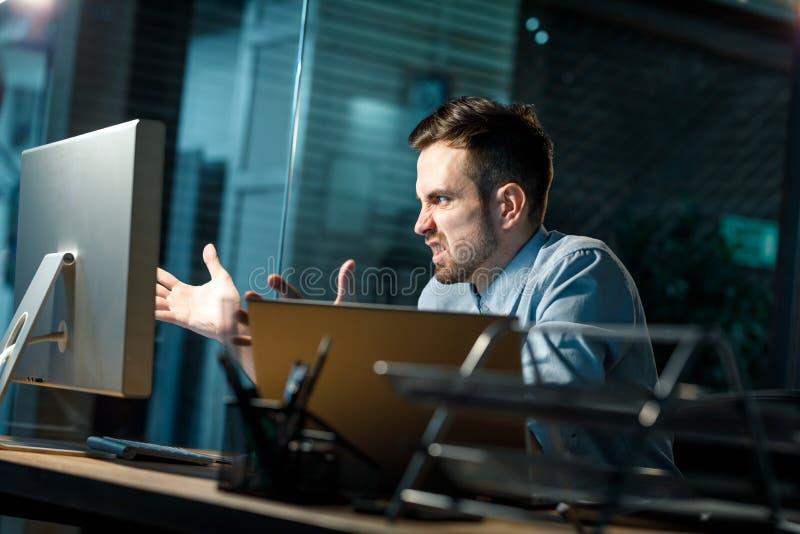 Boze mens met computer in bureau royalty-vrije stock fotografie