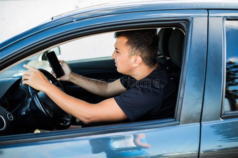 Boze Mensenzitting in auto met het mobiele telefoon in hand texting terwijl het drijven Afgeleide geschokte kerel die zijn smartp stock afbeelding