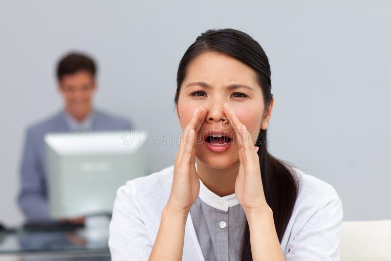 Boze onderneemster die in het bureau schreeuwt stock foto