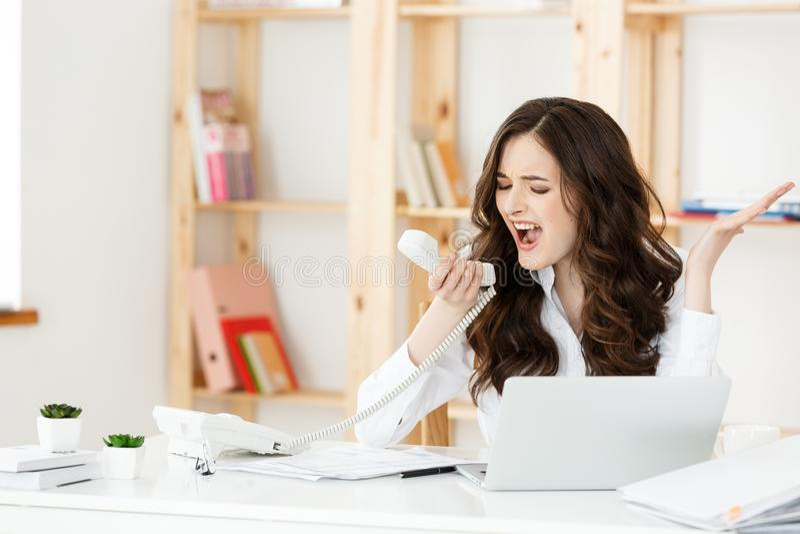 Boze onderneemster die op telefoon in bureau schreeuwen stock foto