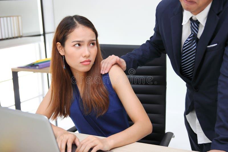 Boze ongelukkige Aziatische secretaressevrouw die hand` s werkgever wat betreft haar schouder in werkplaats kijken Seksuele kwell stock afbeeldingen