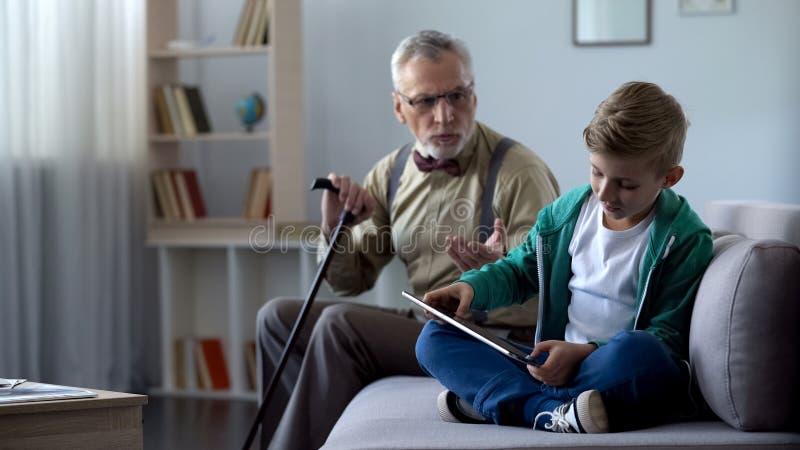 Boze opa berispende kleinzoon voor het spelen videospelletje op tablet, generatiekloof stock foto