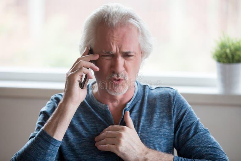 Boze oude mens die bespreking over celtelefoon hebben stock foto