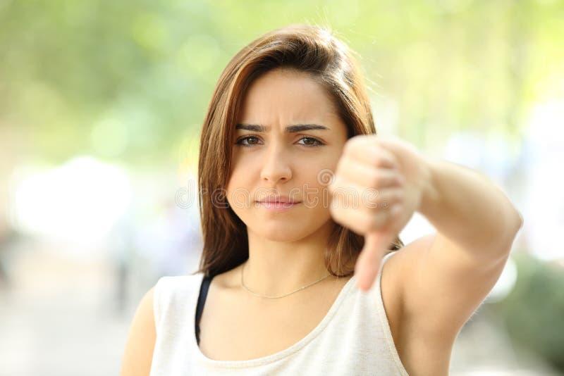 Boze tiener die met neer duim weigeren stock afbeelding