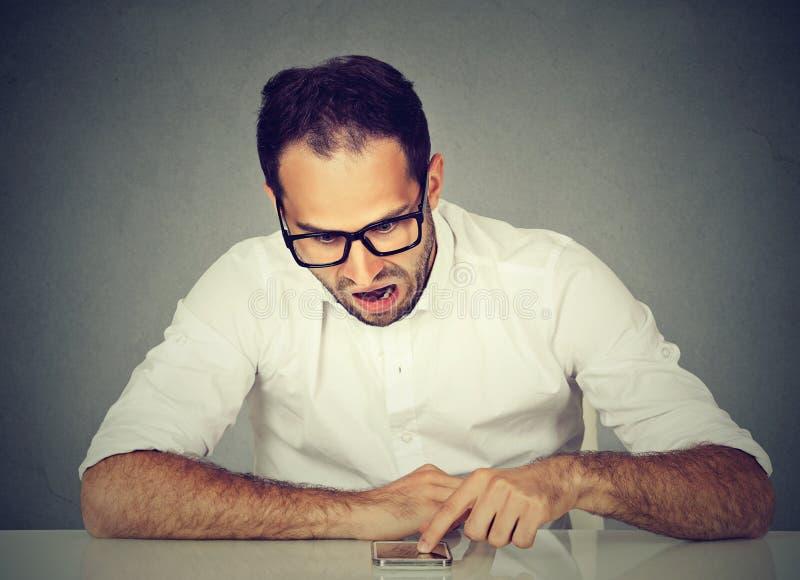Boze verstoorde jonge mens die zijn smartphone gebruiken stock foto's