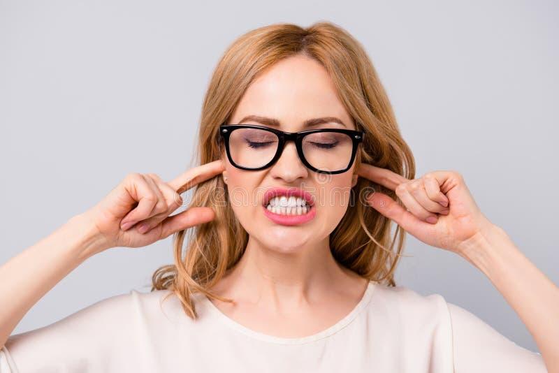 Boze vrij jonge vrouw in bril die haar oren behandelen met FI royalty-vrije stock foto