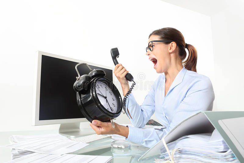 Boze vrouw bij telefoon in bureau met klok, computer stock afbeelding