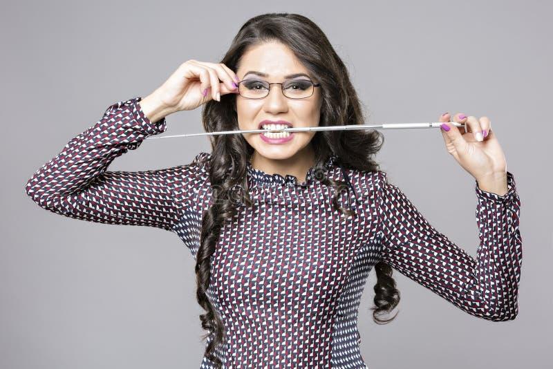 Boze vrouw die glazen dragen die een potlood bijten stock afbeeldingen