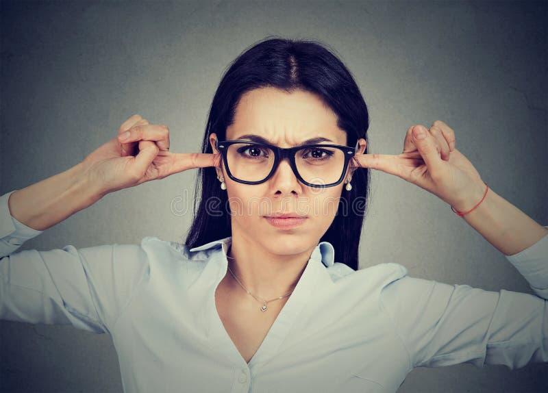 Boze vrouw die haar die oren met vingers stoppen door iemand worden geërgerd stock afbeelding