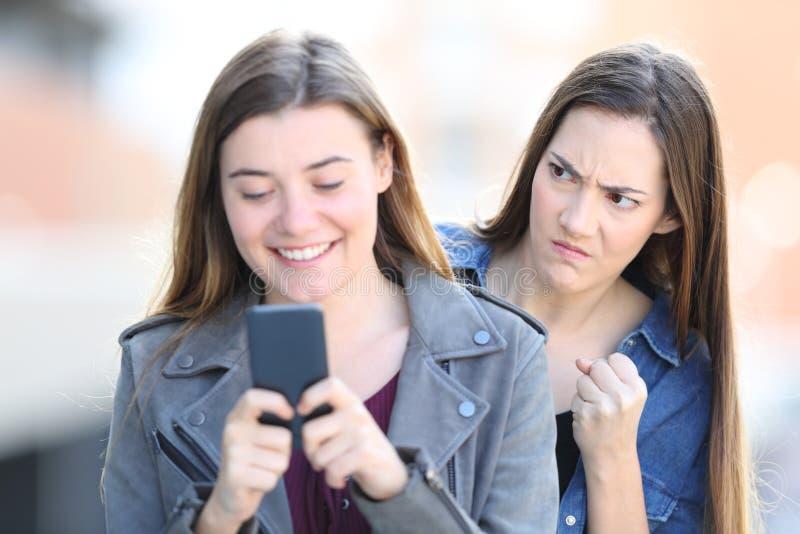 Boze vrouw die haar vriend spioneren die telefoon met behulp van stock foto
