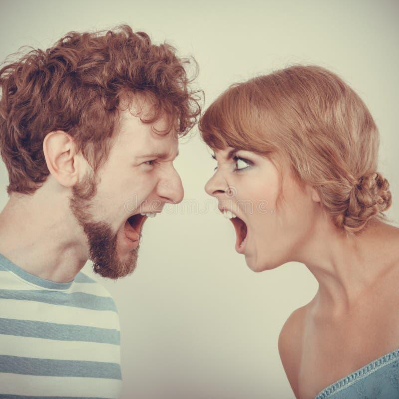 Boze vrouw en man die bij elkaar schreeuwen stock foto's