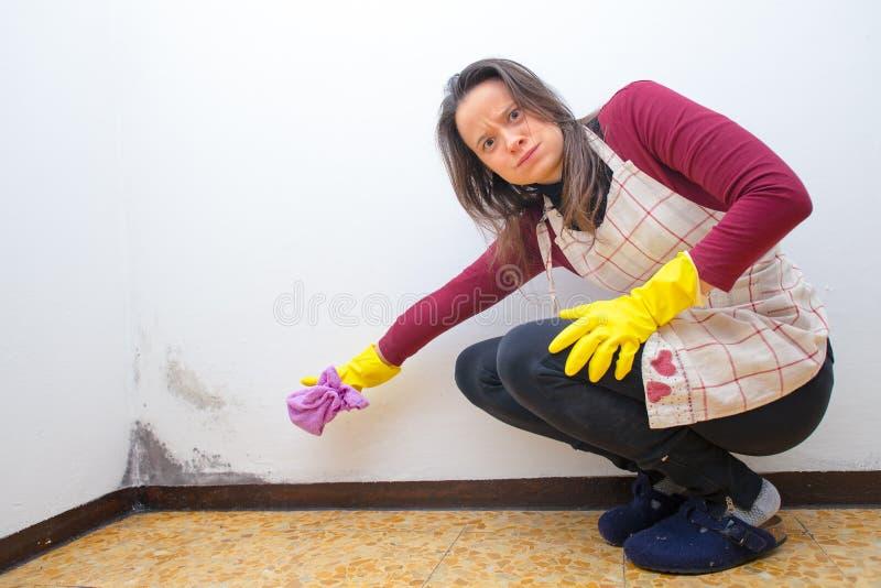 Boze vrouw omdat zij vorm op de muren van het huis vindt stock afbeeldingen