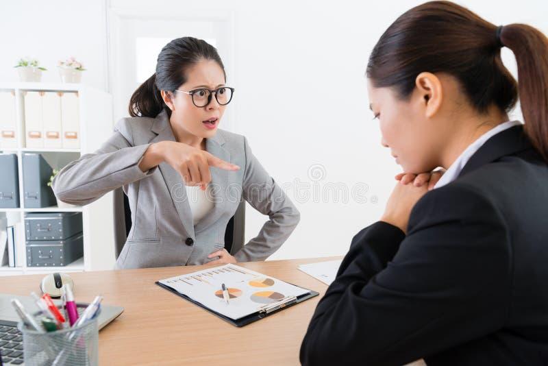 Boze vrouwelijke manager die schuld richten haar werknemer royalty-vrije stock foto