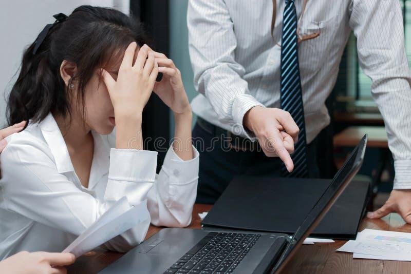 Boze werkgever die jonge Aziatische vrouw met handen op gezicht in bureau beschuldigen royalty-vrije stock afbeeldingen