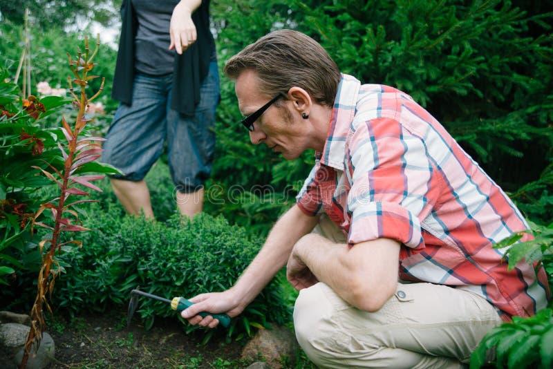 Boze wiffe maakt haar echtgenootwerk bij de tuin royalty-vrije stock afbeelding