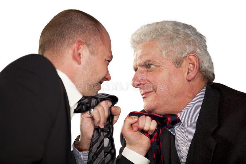 Boze zakenlieden tearing bij hun banden stock afbeeldingen