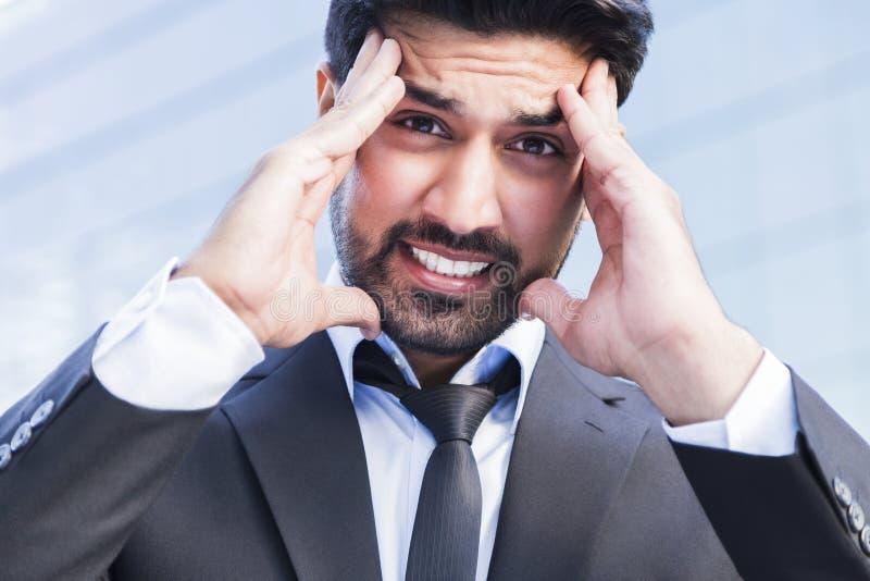 Boze zakenman of arbeider die zich in kostuum met hand op hoofd bevinden stock fotografie