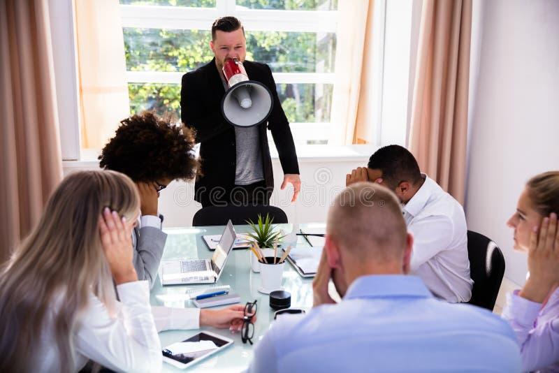 Boze zakenman die door megafoon schreeuwen stock foto