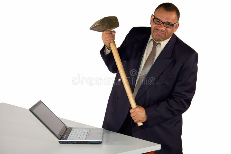 Boze zakenman die laptop met voorhamer raakt stock fotografie
