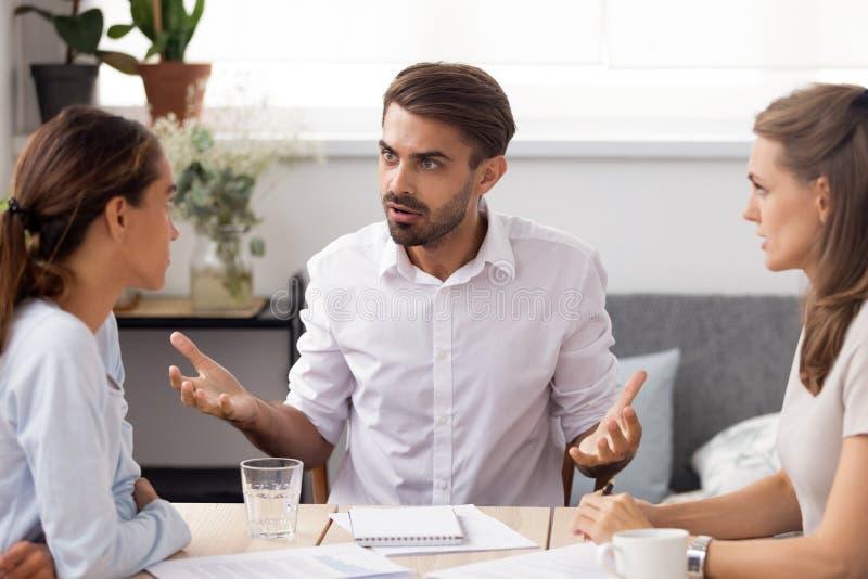 Boze zakenman die met vrouwelijke ondergeschikt op groeps commerci?le vergadering debatteert stock afbeeldingen