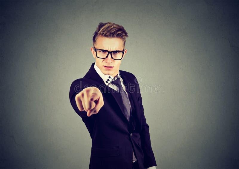 Boze zakenman die vinger richten op camera die iemand beschuldigen royalty-vrije stock afbeelding