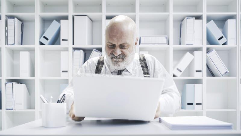 Boze zakenman die zijn laptop breken stock foto's