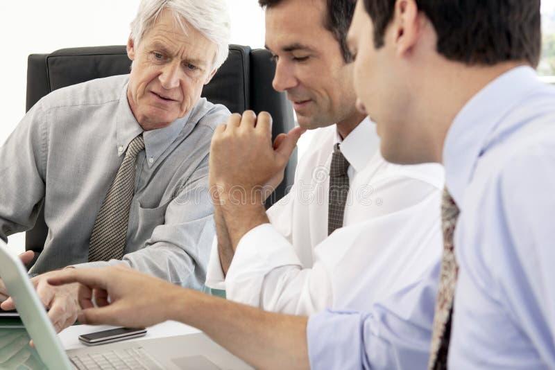Bräde av den företags ledaren som arbetar på datoren arkivbild