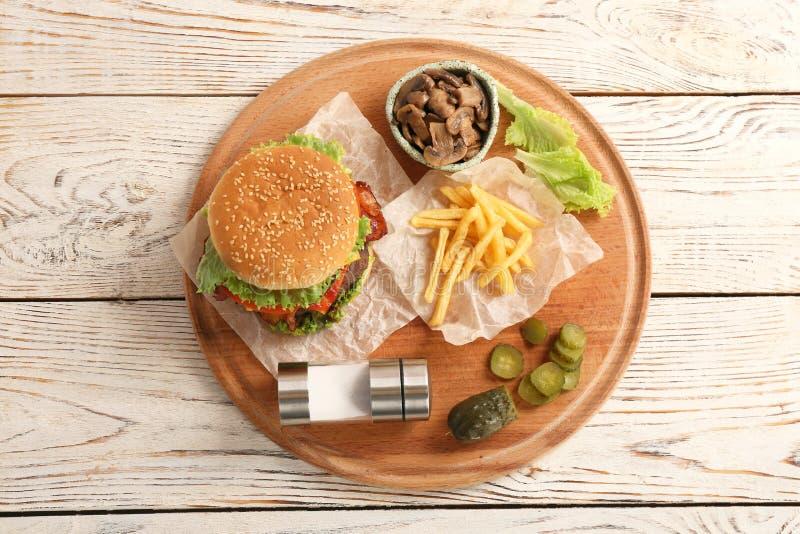 Bräde med den smakliga hamburgaren, franska småfiskar och grönsaker på trätabellen fotografering för bildbyråer