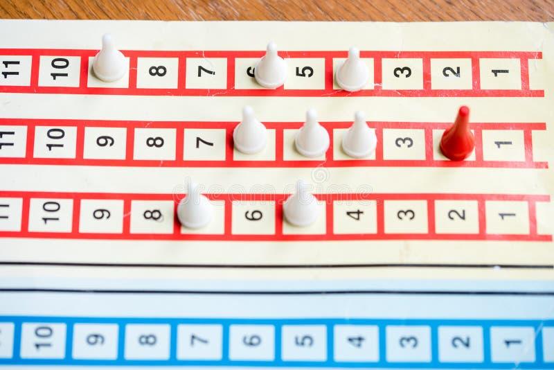 brädeleken med färg pantsätter, den röda chipen är i täten, vita konkurrenter royaltyfri fotografi