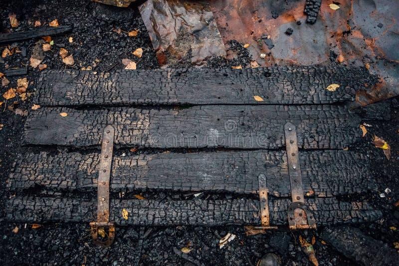 Bränd ned trädörr av det fullständigt brända huset på jordningen arkivbilder