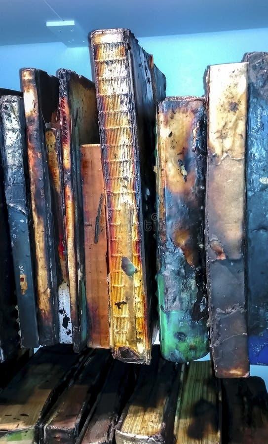Brända gamla böcker på hyllan, upprätt arkivfoto