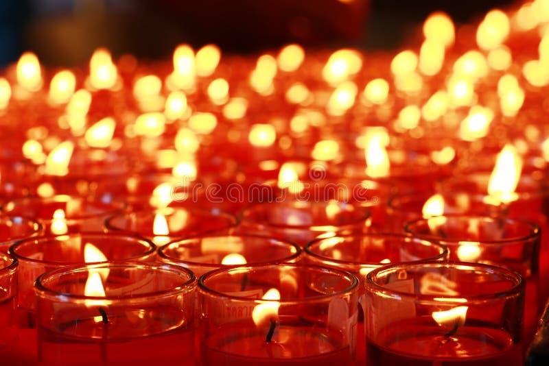 Bränna för många rött stearinljus royaltyfri fotografi
