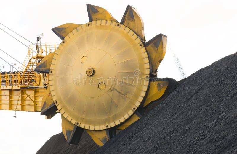 Bränna till kol hinkmaskineri som staplar kolet i högar arkivbilder