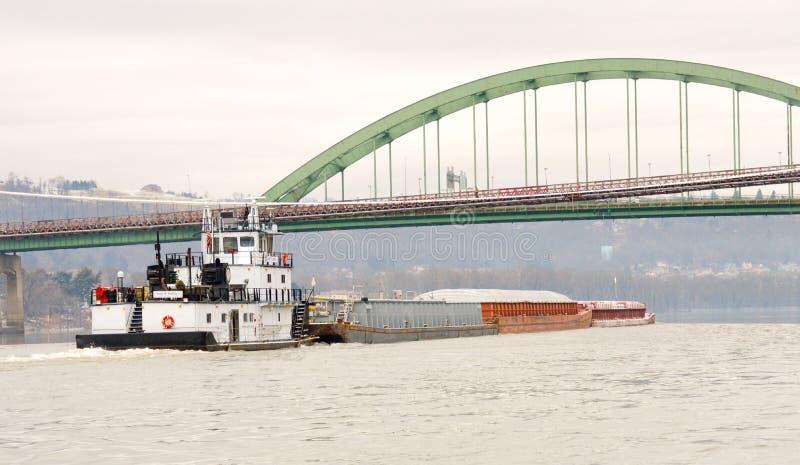 Bränna till kol pråm som går ner Ohioet River under en bro royaltyfria bilder