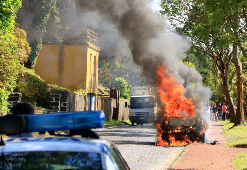 Brännande bil på vägen med polisen fotografering för bildbyråer
