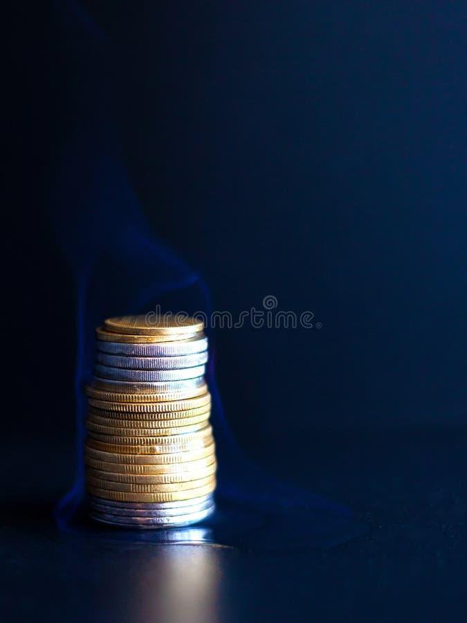 Brännande dollar och euro i mynt en brinnande finansiell pyramid av pengarskrivning med stora bokstäver arkivfoto