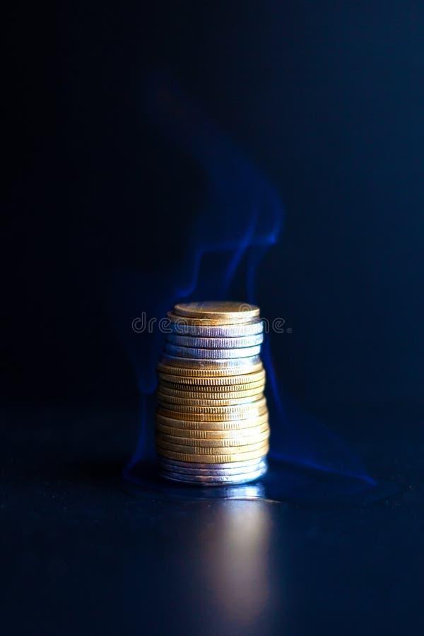 Brännande dollar och euro i mynt en brinnande finansiell pyramid av pengarskrivning med stora bokstäver royaltyfria foton