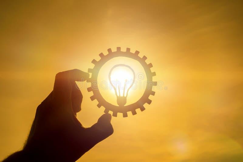Brännande lampidé i ett kugghjul på en bakgrund av solen som rymmer en affärsmans hand royaltyfria bilder