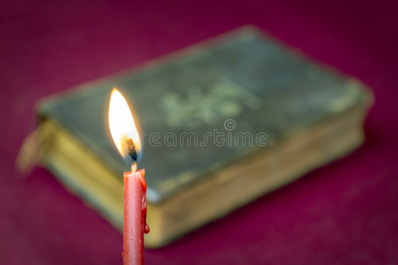 Brännande röd kyrklig stearinljus och suddig helig bibel bakom arkivfoton