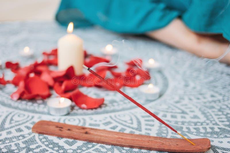 Brännande röd pinne för rökelse på stearinljus bakgrund och övande yoga för kvinna royaltyfria foton