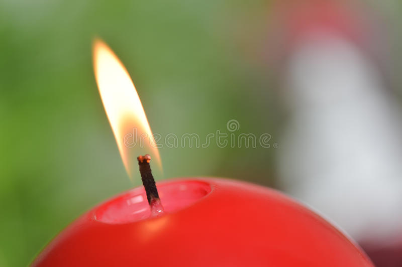 Brännande stearinljus gräsplan och rött royaltyfri foto