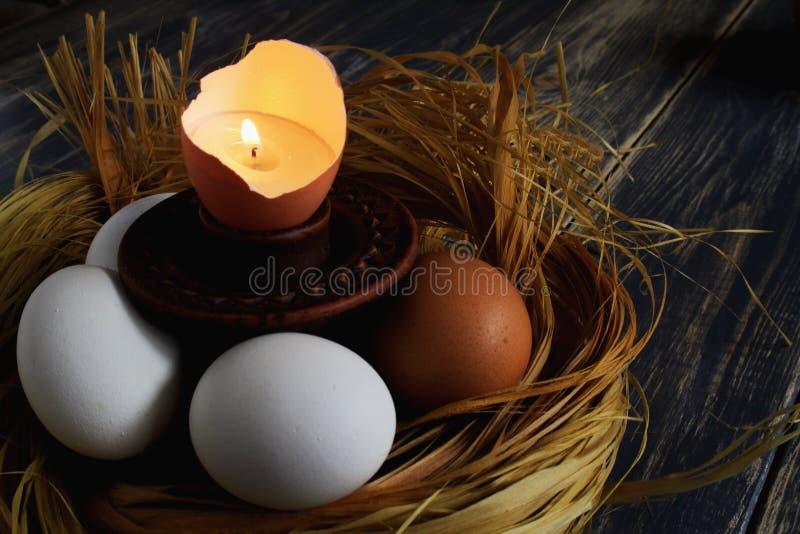 Brännande stearinljus i äggskal som symbol av liv på den keramiska ljusstaken bland ägg i rede av bast på mörk gammal träbakgrund royaltyfri foto